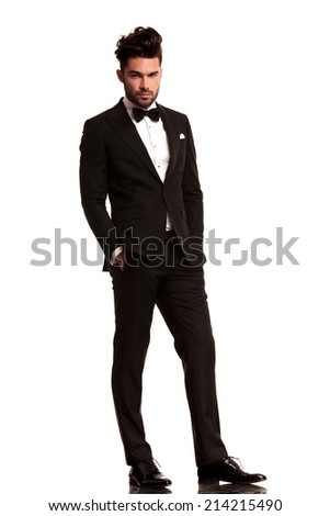 relaxed elegant man in tuxedo looking at the camera on white background - stock photo