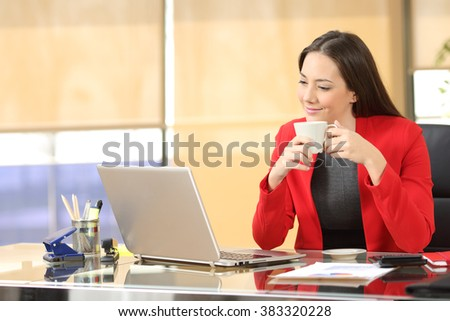Relaxed entrepreneur working online watching a laptop and holding a cup of coffee sitting in a desk at office - stock photo
