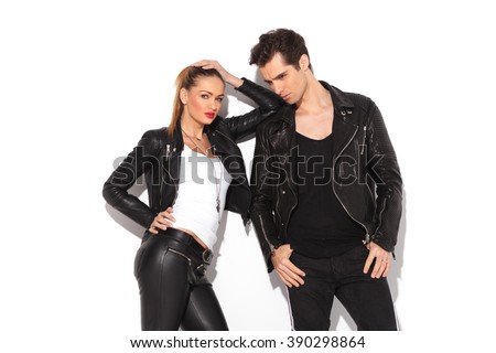 relaxed fashion couple in leather clothes posing in studio, woman leaning on her lover's shoulder