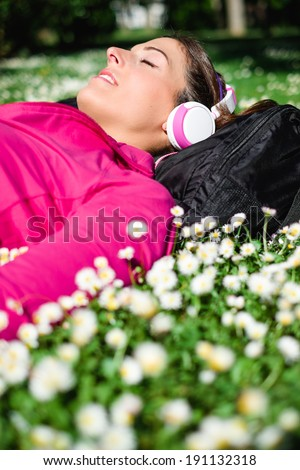 Relaxed female athlete resting and listening music with headphones after workout. Woman lying down on grass and spring flowers. Healthy lifestyle and happiness concept. - stock photo