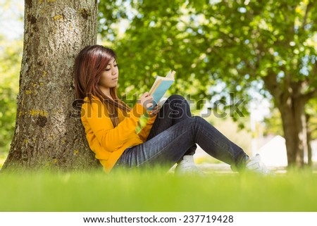 Relaxed female college student reading book against tree trunk in the park - stock photo