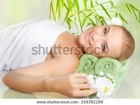 Relaxed female lying down in spa salon on massage table, enjoying nice beauty procedure, healthy lifestyle, wellness concept - stock photo