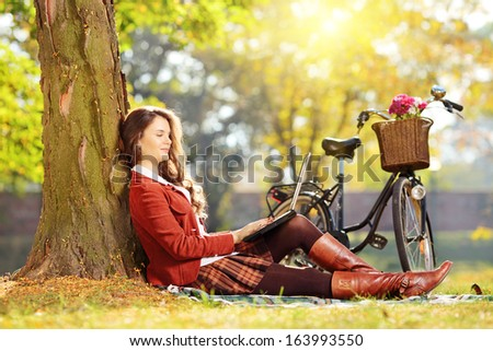 Relaxed female working on a laptop seated on a grass in a park on a sunny day - stock photo