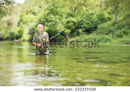 Relaxed fisherman fishing in a river with a fishing rod on a sunny day