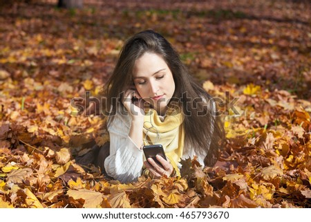 Relaxed girl lying on autumn leaves and listening music on headphones. Young woman in park using smart phone and enjoying in music during fall season.