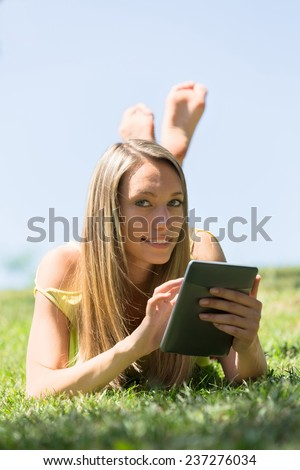 Relaxed girl lying on grass in meadow enjoying reading  ereader - stock photo