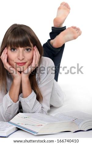 Relaxed girl reading encyclopedia - stock photo