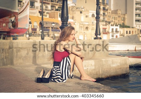 Relaxed girl sitting at the harbor - stock photo