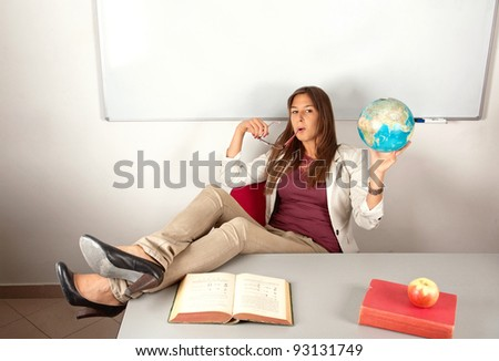 Relaxed girl teacher sitting with legs on table and holding globe