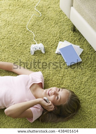 Relaxed girl using mobile phones while laying on green carpet at home. Mobile technology concept. - stock photo