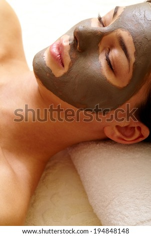 Relaxed girl with clay or mud mask on face for pore cleaning - stock photo