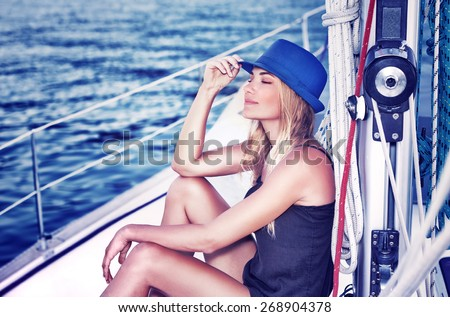 Relaxed girl with closed eyes of pleasure sitting on sailboat, enjoying mild sunlight, fashion model in luxury sea cruise, summer vacation and travel - stock photo
