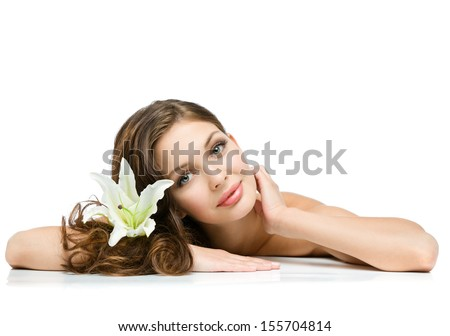 Relaxed girl with lily in hair lies, isolated on white. Concept of natural beauty and youth - stock photo