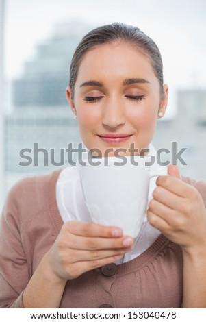 Relaxed gorgeous businesswoman in bright office holding cup of coffee