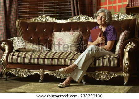 Relaxed grandmother sitting on the couch at home - stock photo