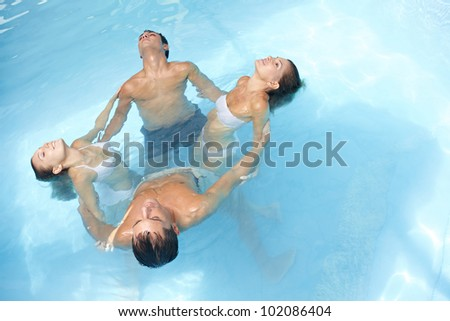 Relaxed group doing water yoga in blue swimming pool - stock photo