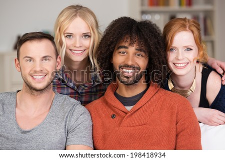 Relaxed group of four young multiracial friends posing together on a couch in the living room smiling happily at the camera