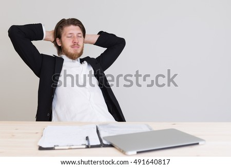 relaxed handsome bearded man in formalwear sitting with feet up on desk at company office, taking break from paperwork