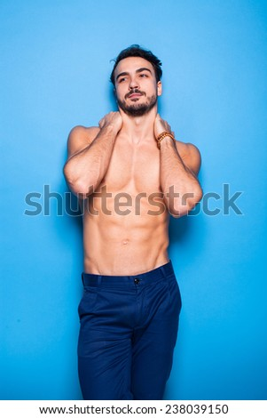 relaxed handsome man with beard standing shirtless on blue background holding his neck with hands - stock photo