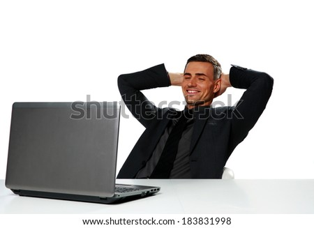 Relaxed happy businessman sitting at the table with laptop isolated on a white background - stock photo