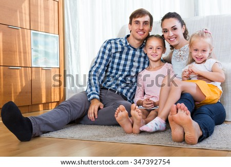 Relaxed happy family of four persons posing in domestic interior