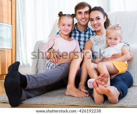 Relaxed happy family of four persons posing in the domestic interior