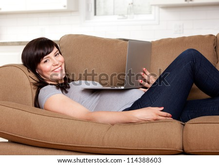 Relaxed happy pregnant woman sitting on sofa with laptop computer