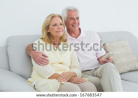 Relaxed happy senior couple with remote control sitting on sofa in a house