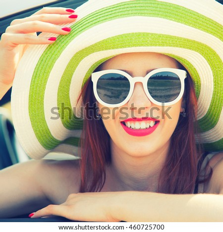 Relaxed happy woman on summer roadtrip travel vacation leaning out car window in white glasses
