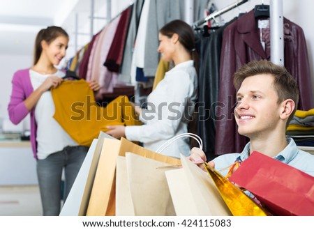 Relaxed husband sitting with purchases, positive  wife buying more clothes