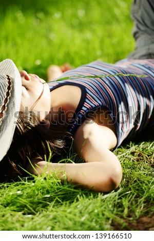 Relaxed kid resting on summer park grass meadow - stock photo