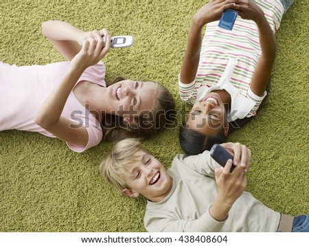 Relaxed kids using mobile phones while laying on green carpet at home. Mobile technology concept. - stock photo