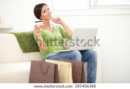Relaxed lady using a laptop for electronic payment while holding a credit card - stock photo
