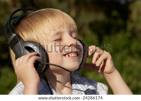 Relaxed  little  boy listening music in park - stock photo