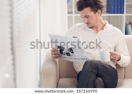 Relaxed man drinking coffee while reading newspaper