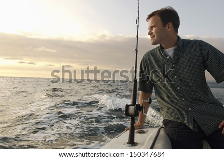 Relaxed man fishing on yacht at sea - stock photo