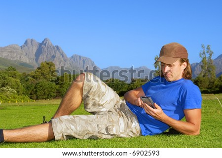 Relaxed man lies on grass with smartphone or computer - and misty mountains are background. Shot in Stellenbosch, South Africa.