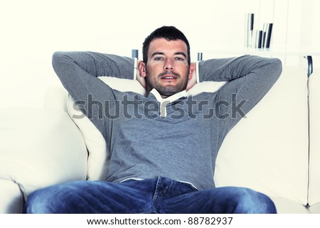 relaxed man on his sofa at home - stock photo