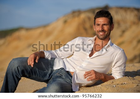relaxed man seated at the beach on the sand at sunset - stock photo