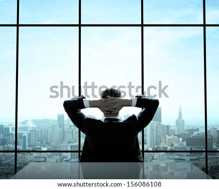 relaxed man sitting in office - stock photo