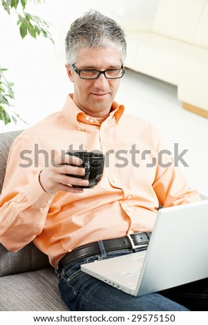 Relaxed man sitting on couch, drinking coffee and using laptop computer.