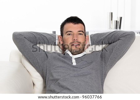 relaxed man sitting on sofa at home