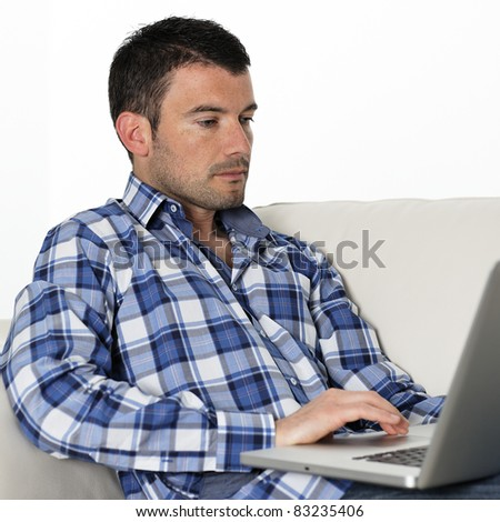 relaxed man sitting on sofa with computer - stock photo