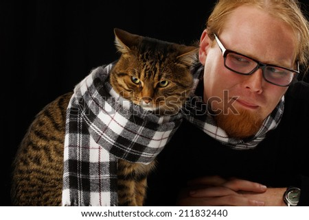 Relaxed man sitting with cat in his scarf. Shallow DOF. Focus on cat. - stock photo