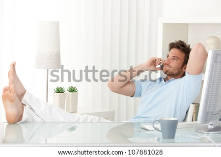 Relaxed man sitting with feet up on desk at home, talking on mobile phone, smiling. - stock photo