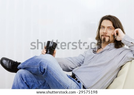 Relaxed man talking on mobile phone, sitting on a couch and holding a coffee cup in hand. - stock photo