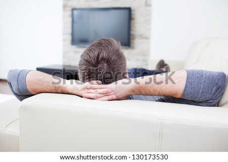 Relaxed man watching tv and lying on the couch.