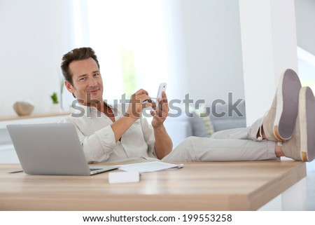 Relaxed man working from home and using smartphone - stock photo
