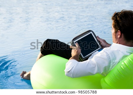 Relaxed man working with tablet PC on pool