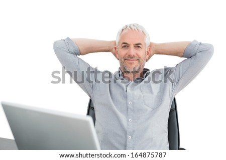 Relaxed mature businessman sitting with hands behind head with laptop against white background